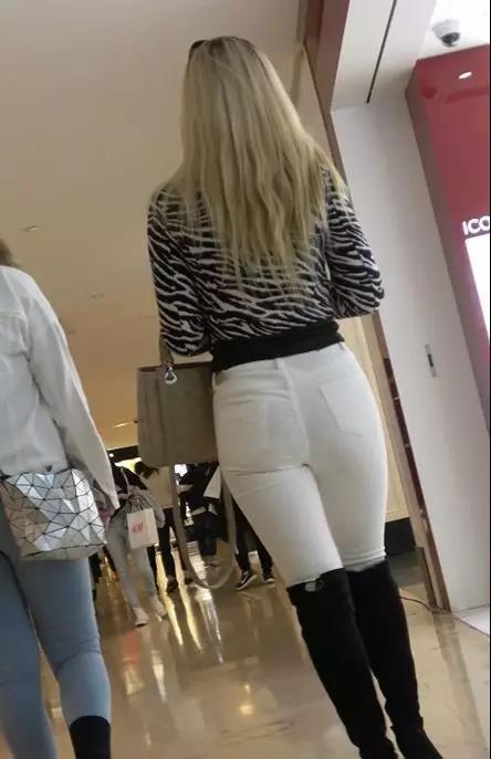 街拍:穿紧身白裤和黑色长筒靴的美臀好身材性感美女
