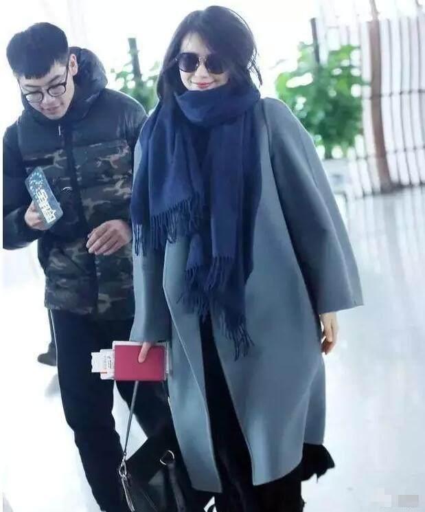高圆圆搭配一条深蓝色的围巾,身穿一件雾霾蓝色的长款外套现身机场